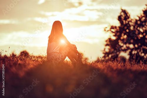 Obraz na plátně Silhouette of a woman sitting on a field.