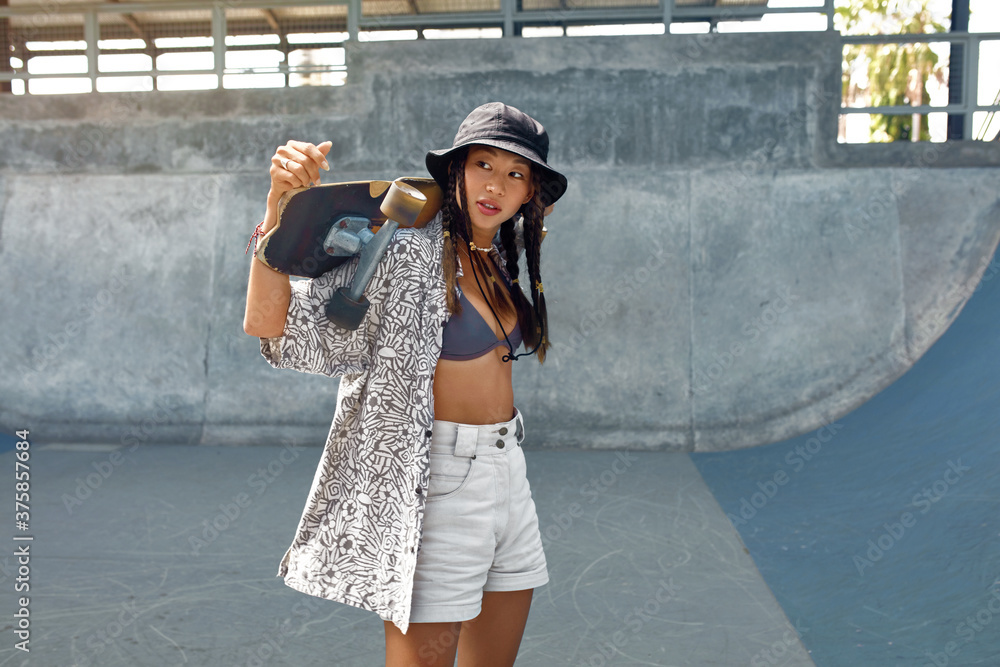 Fototapeta Skateboarding. Asian Girl In Casual Clothes With Skateboard Against Concrete Wall At Skatepark. Urban Sport As Hobby Of Active Teens. Skater Subculture And Summer Activity As City Lifestyle.