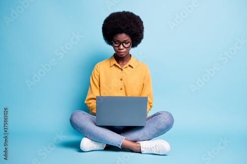Full body size photo of black skin big volume hairstyle woman sit floor hold netbook serious calm comfort work freelance project wear specs jeans yellow shirt isolated blue color background