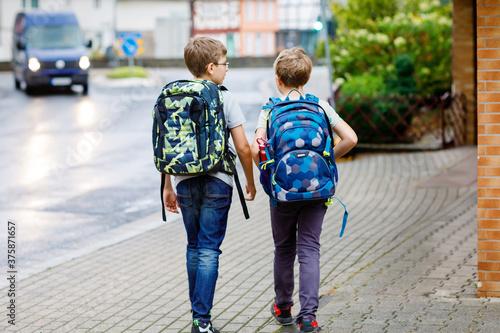 Fototapeta Two little kid boys with backpack or satchel