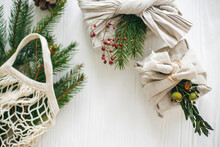 Zero Waste Christmas Holidays. Stylish Christmas Gifts Wrapped In Linen Fabric With Green Branch And Reusable Shopping Bag With Green Spruce On Rustic Wooden Background.