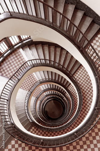 Fototapety, obrazy: Brown round spiral staircase with white walls black railings with patterns and checkered floor down view
