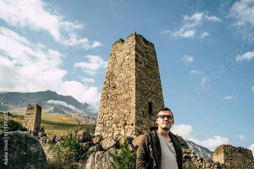 Photo Traveler standing near ancient ruins in mountains