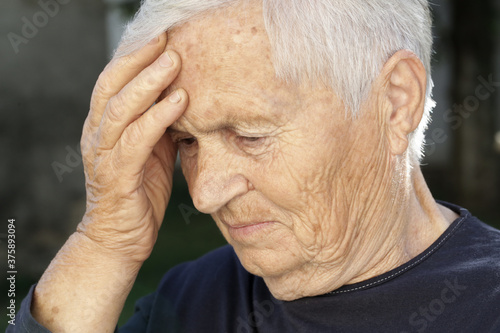 Photo Senior caucasian woman holds her hand to her forehead