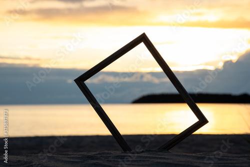 Fényképezés Photo frame in sand on the beach. Beautiful sunset background.