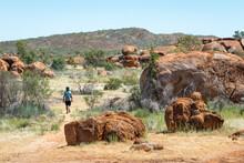 Male Tourist Walking Across The Devils Marbles, Sacred Aboriginal Place With Massive Granite Boulders. Symbol Of Australia's Outback. Karlu Karlu (round Boulders), Tennant Creek, NT, Australia