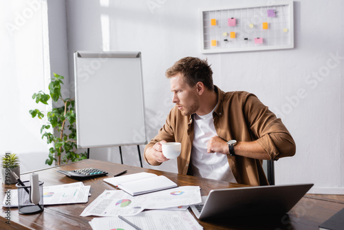 Selective focus of young businessman coughing and holding coffee cup at working Fotobehang