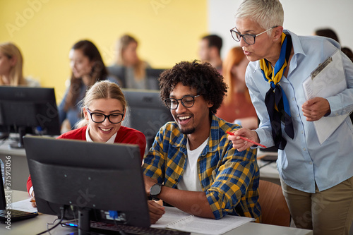 Teacher looking pupils task on theirs computer Fotobehang