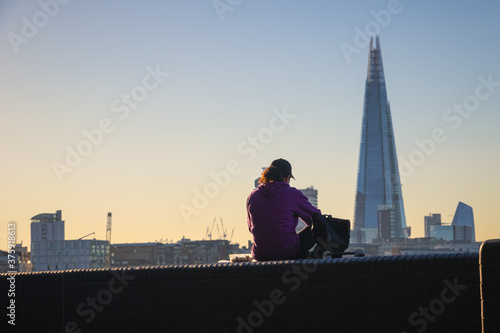 Back view of a female sitting on Thames embankment with The Shard in the backgro Canvas Print