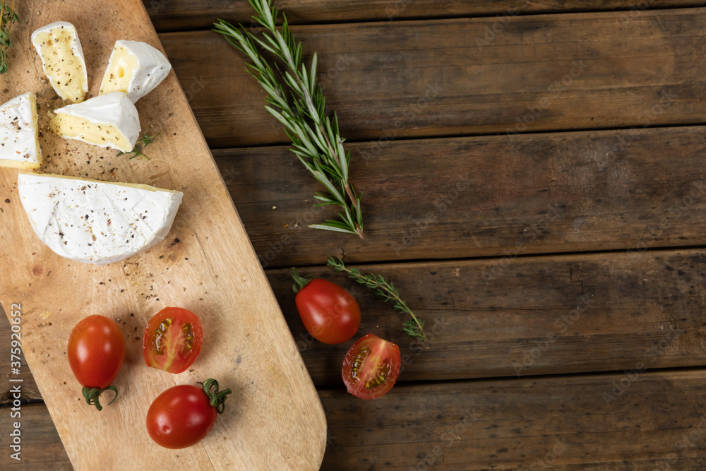 View of a wooden cutting board with cherry tomatoes and cheese arranged on a on a textured wooden