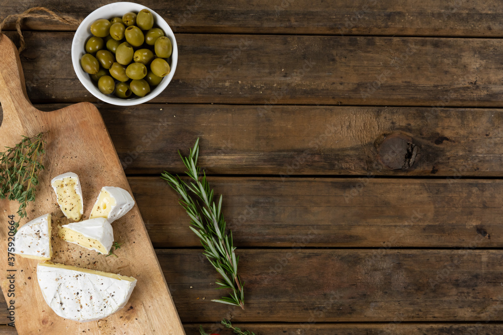 View of a wooden cutting board with cheese on a textured wooden surface with thyme and bowl of olive