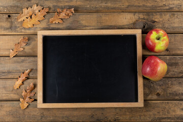 View of a black board surrounded by apples and leaves on wood table background