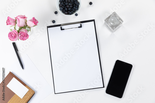 View of a notebook and phone with flowers and perfume on white background