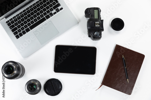 View of school supplies with a laptop and a tablet with a camera and lance in a white background