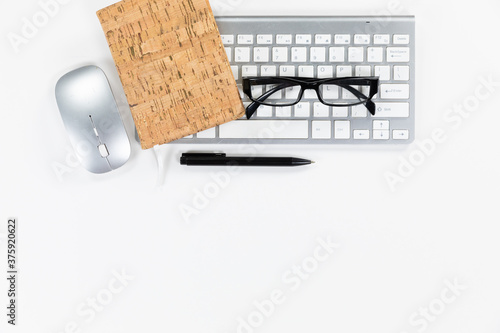 View of a keyword with glasses and a notebook with a pen in a white background
