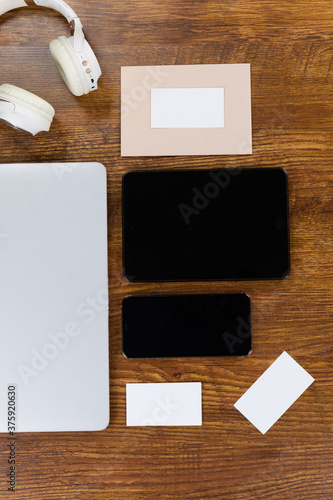 View of a laptop with a tablet and smartphone, an enveoppe and headphone on wood table background