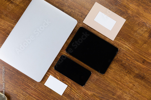 View of a laptop with a tablet and smartphone, an enveloppe and paper on wood table background