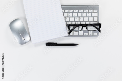 View of a keyword with a notebook, a pen and glasses on white background
