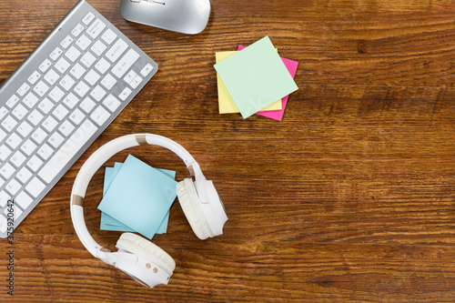 View of a keyword with headphones and small colorful sheets of paper on wood table bakground
