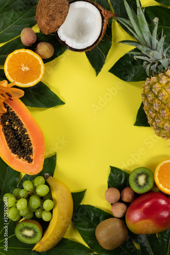 View of a composition with variety of fresh tropical fruits and leafs arranged on a yellow surface