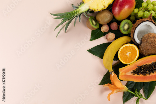 View of a composition with variety of fresh tropical fruits and leafs arranged on a pink surface