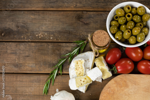 View of a wooden cutting board with bread, cheese, sausage, fruits and wine on a wooden surface