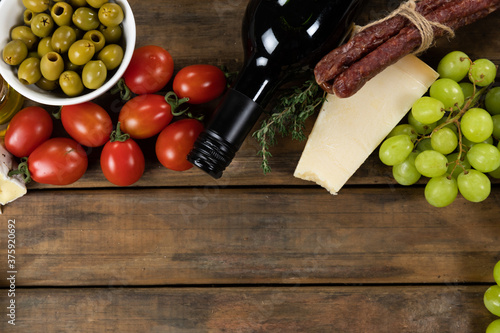 view of a composition with pieces of bread, cheese, sausage, fresh fruits and a bottle of wine on wo