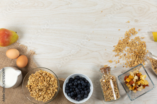 View of a variety of nuts and muesli, bowls of dried and fruits and eggs on wooden surface
