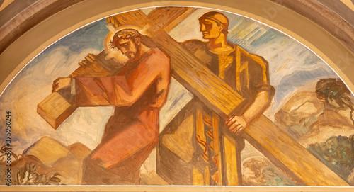 Fotografía BARCELONA, SPAIN - MARCH 3, 2020: The fresco Simon of Cyrene helps Jesus carry the cross in the church Santuario Nuestra Senora del Sagrado Corazon by Francesc Labarta (1960)