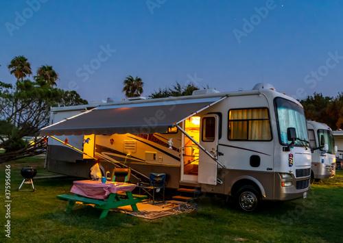 Billede på lærred Rv camping in a Rv resort under the evening sky with lights on the coach
