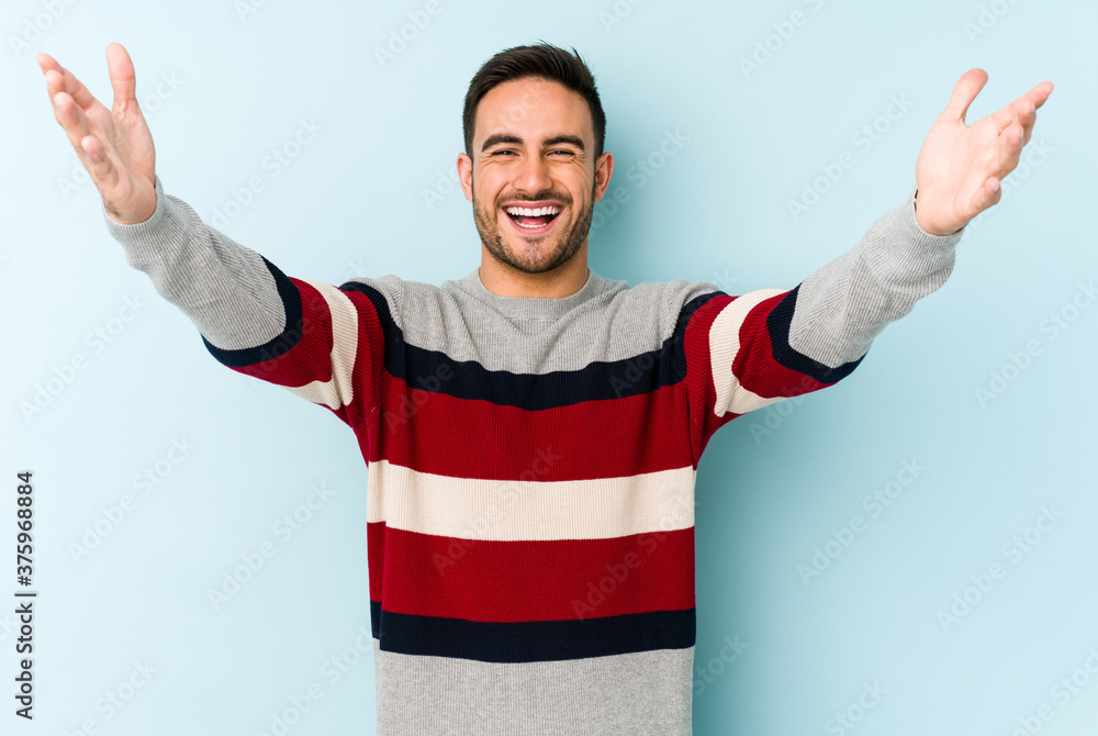 Fototapeta Young caucasian man isolated on blue background celebrating a victory or success, he is surprised and shocked.