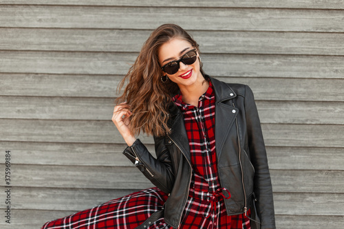 Obraz Cute stylish joyful young woman with red lipstick with positive smile in sunglasses in fashion leather jacket near vintage wooden wall on street. Happy smiling woman model straightens hair in city. - fototapety do salonu