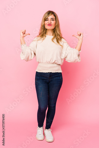 Fototapeta Young blonde caucasian woman standing over a pink background feels proud and self confident, example to follow