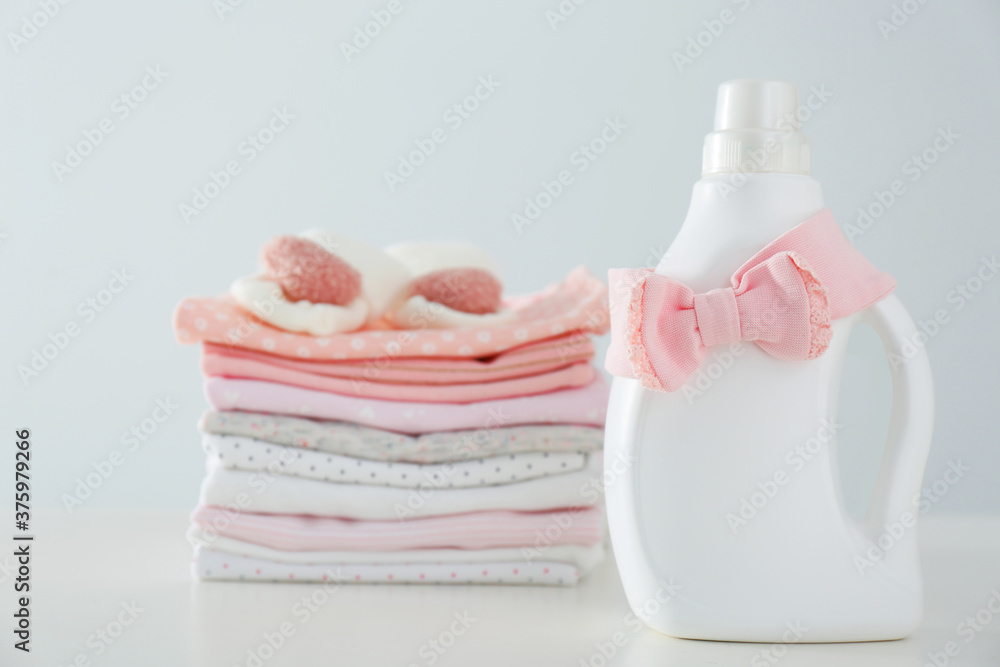 Detergent and children's clothes on white table