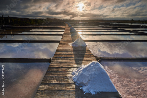 Fotografie, Obraz Traditional salt extraction camp (Salinas) with piles of extracted salt at sunri