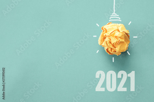 Obraz 2021 Yellow paper light bulb on blue background, innovative business vision and resolution concept - fototapety do salonu