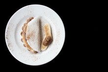 Banana Tapioca With Cinnamon And Chocolate On A White Dish Whit Black Background
