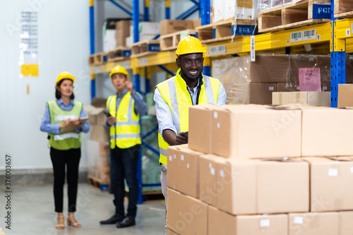 Photo Black Male warehouse worker pulling a pallet truck
