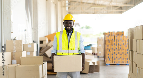 Fényképezés middle aged African American warehouse worker preparing a shipment in large ware