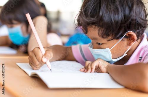 Fotografia school boy wearing  mask and study in classroom