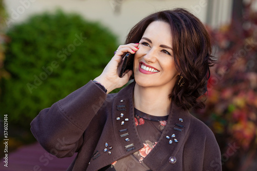 Attractive middle ade woman using smartphone while sitting on a bench in the city park Wallpaper Mural