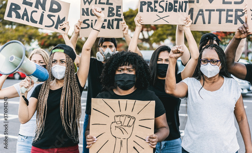 Fototapeta People from different culture and races protest on the street for equal rights - Demonstrators wearing face masks during black lives matter no racism campaign - Focus on left girl face obraz