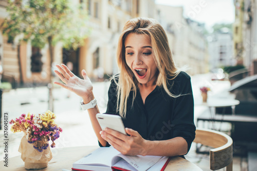 Fotografiet Excited female blogger with happiness expression on face impressed with received