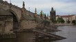 Charles Bridge from the role of 1402 on the flowing river Vltava in the center of Prague. in the early evening after sunset the sky is overcast. in the Czech Republic