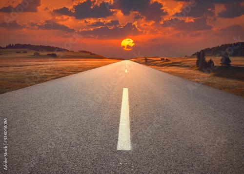 Fototapeta Open highway in mountain range towards the sunset