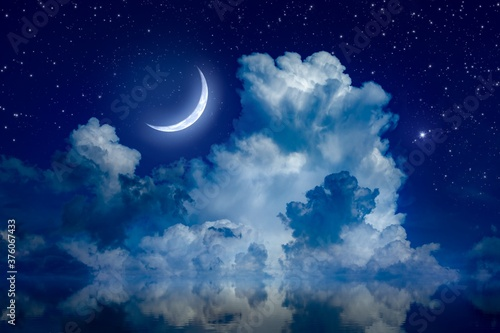 Big crescent moon and clouds in night starry sky is reflected in calm sea Fototapet
