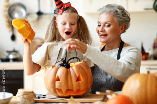 Grandmother and granddaughter putting spider in pumpkin.