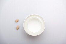 An Asian Hand Holding Two Pills And A Paper Cup Filled With Water