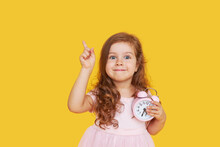 Time For A Party. A Pensive Cute Child In A Fancy Dress Holds A Small Alarm Clock In His Hands And Shows Up. Yellow Studio Background..