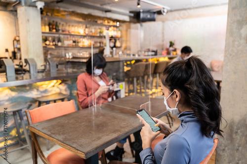 Fototapeta New normal customer dine in restaurant. Waitress with mask serve food. obraz